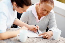 caregiver helping an old woman with word puzzle