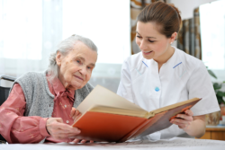 old lady with her caregiver reading book